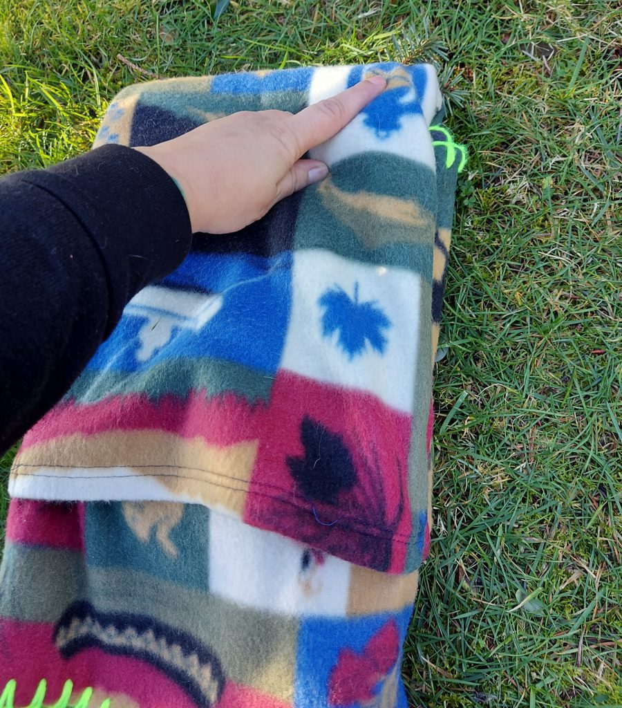 hand pointing to upper corner of folded blanket on the grass