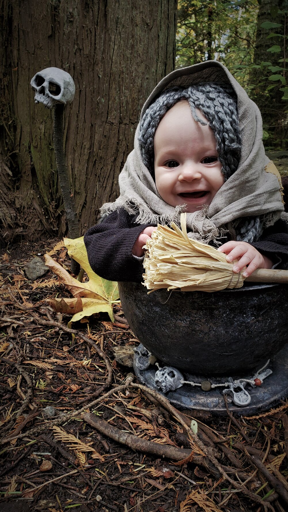 Baby Baba Yaga in mortar on ground in woods