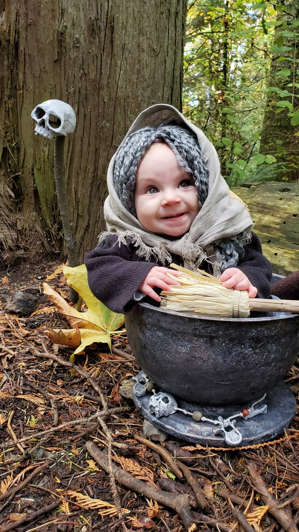 Baby Baba Yaga in mortar prop on ground in woods