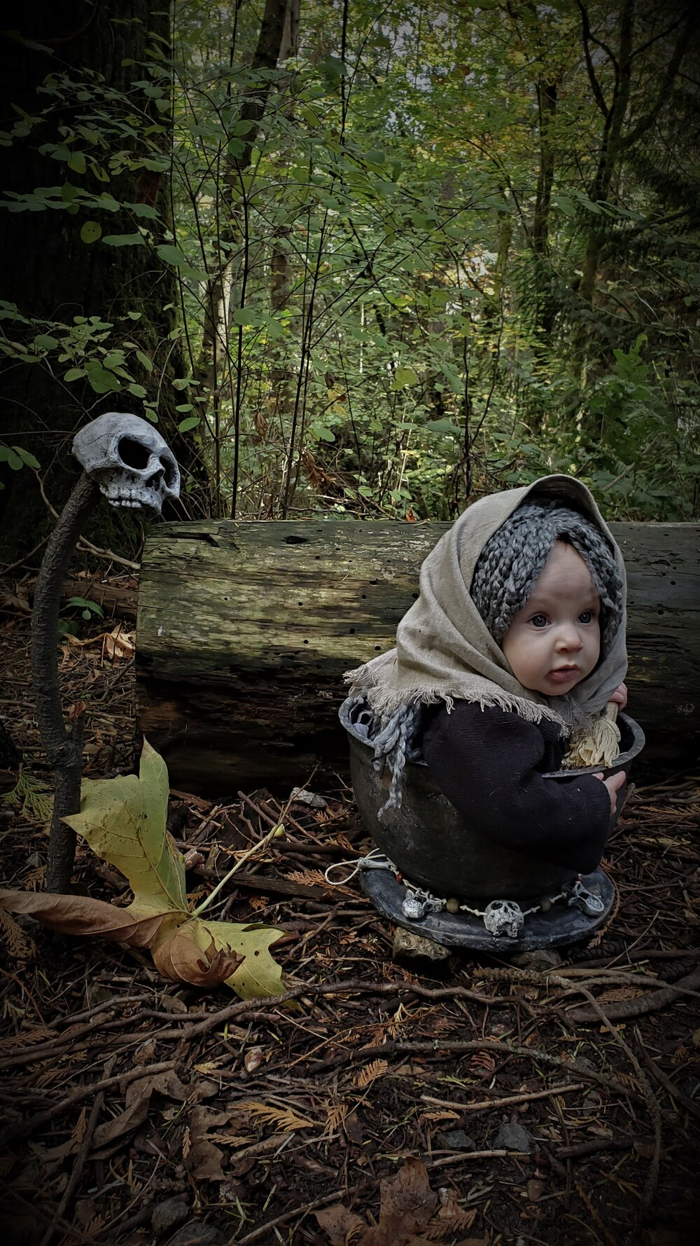 Baby Baba Yaga on ground in woods riding in mortar