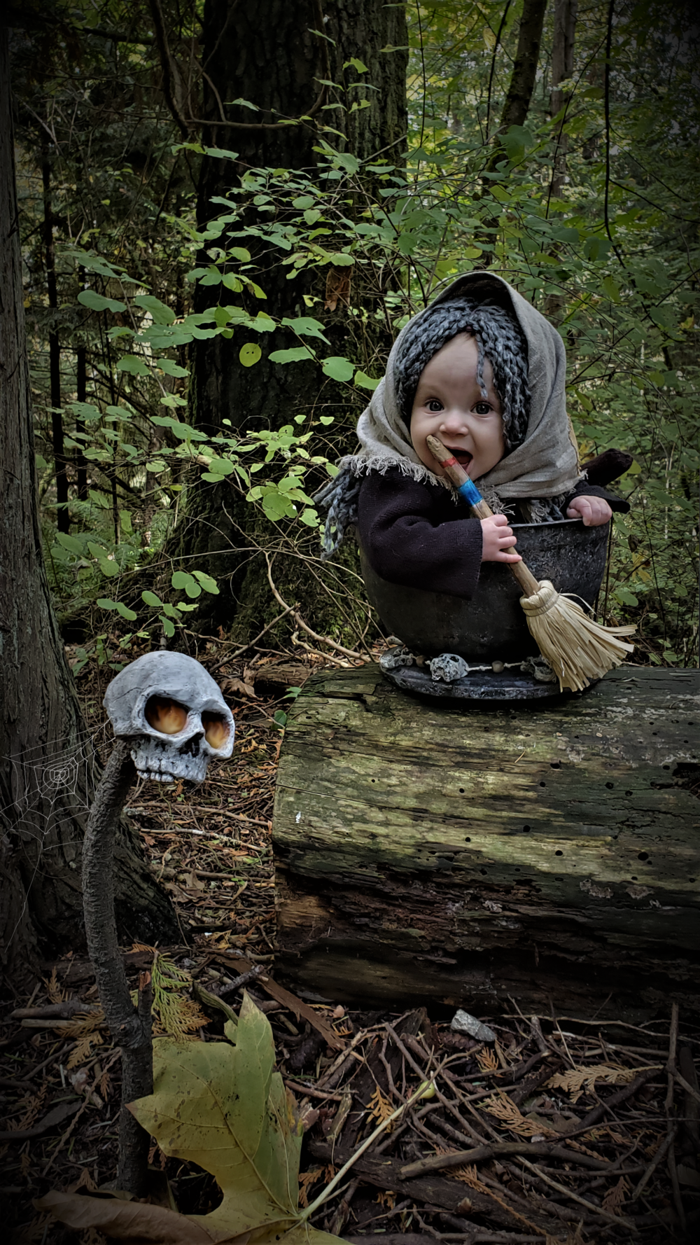 baby Baba Yaga in mortar on log in woods chewing on broom