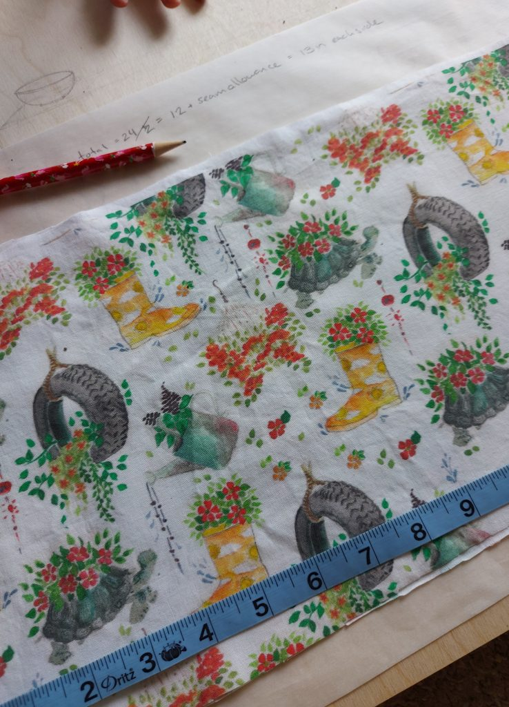 fabric with flower containers on wood  with pencil and measuring tape