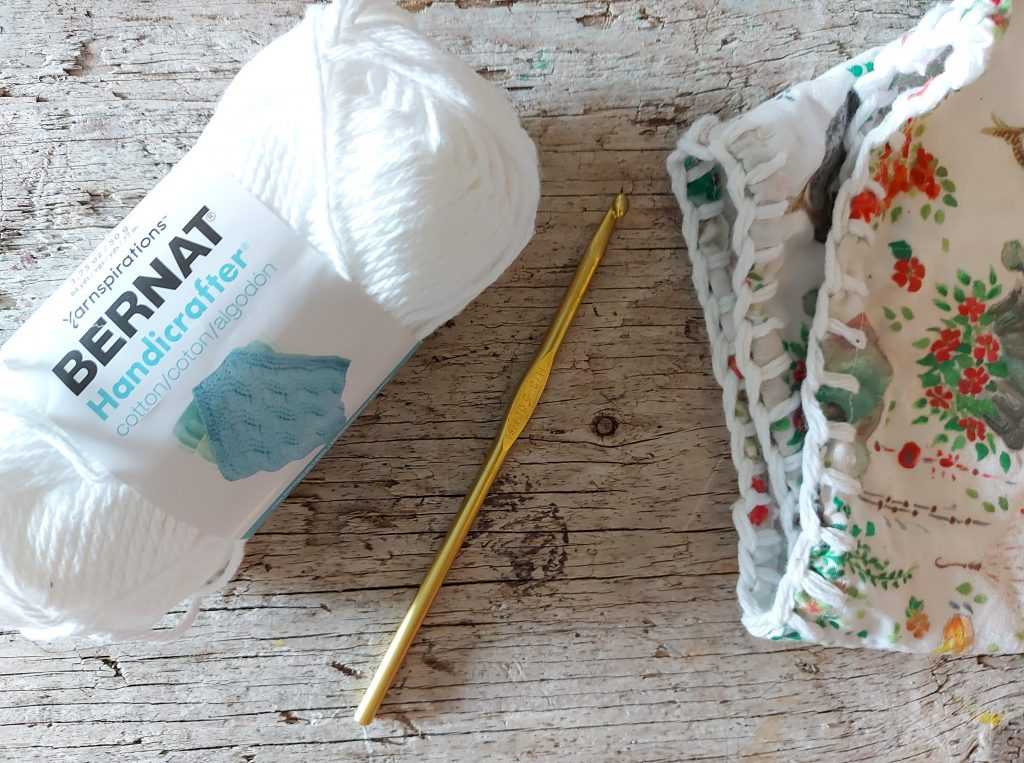 yarn, crochet hook, fabric all laying on wooden background