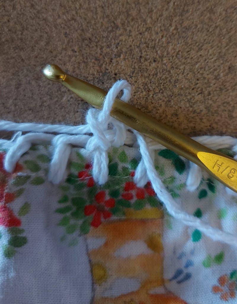 crochet hook casting onto crochet and fabric tank top bottom
