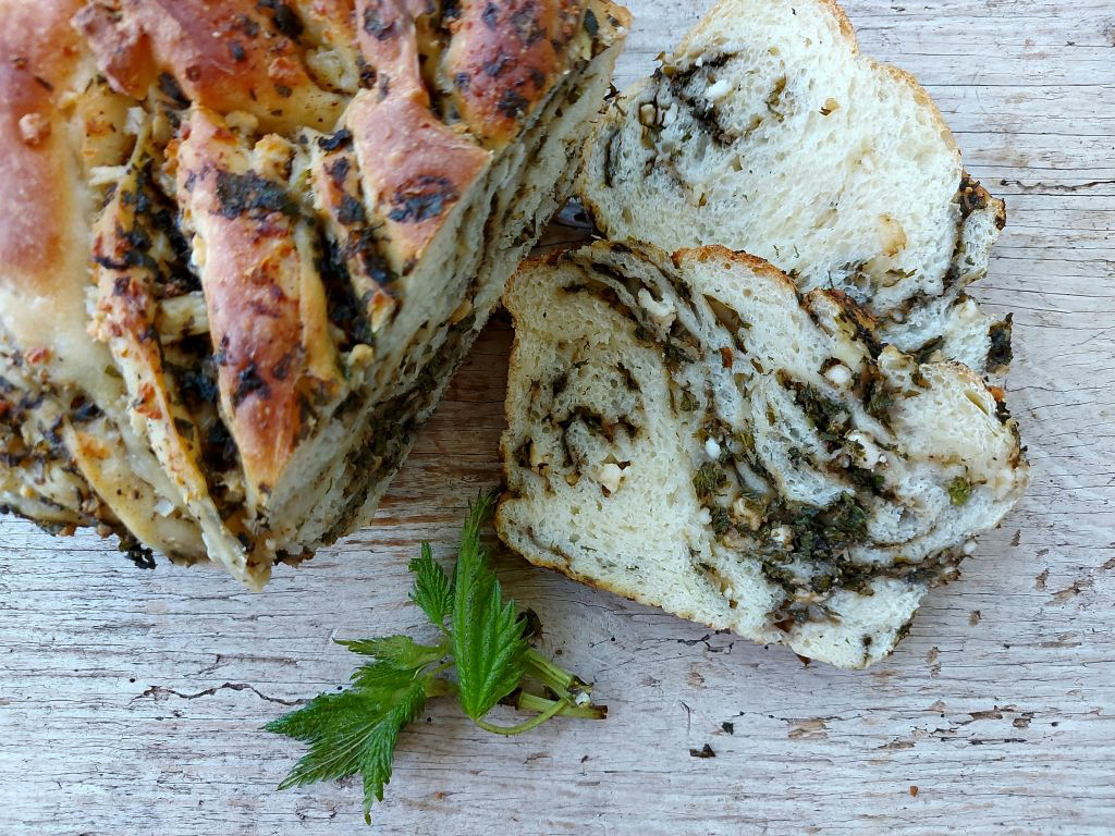 stinging nettle and feta twist bread loaf cut up on wooden background