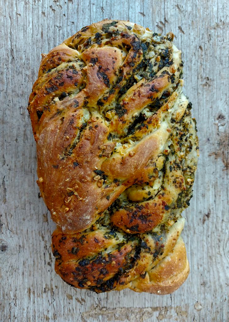 stinging nettle and feta twist bread on wooden background top down