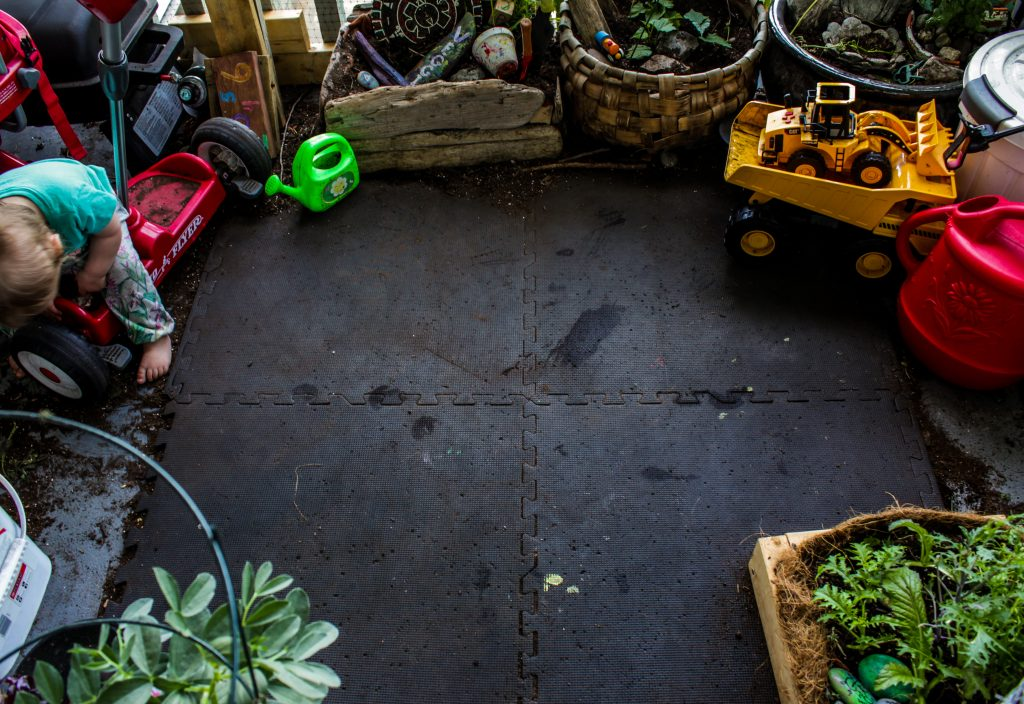 deck garden play mat surrounded by toys and plants