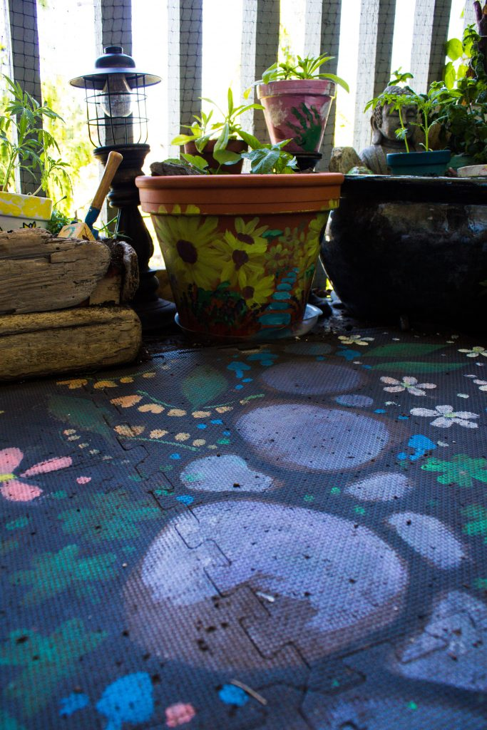 Garden containers and foam mat painted with a garden pathway and flowers