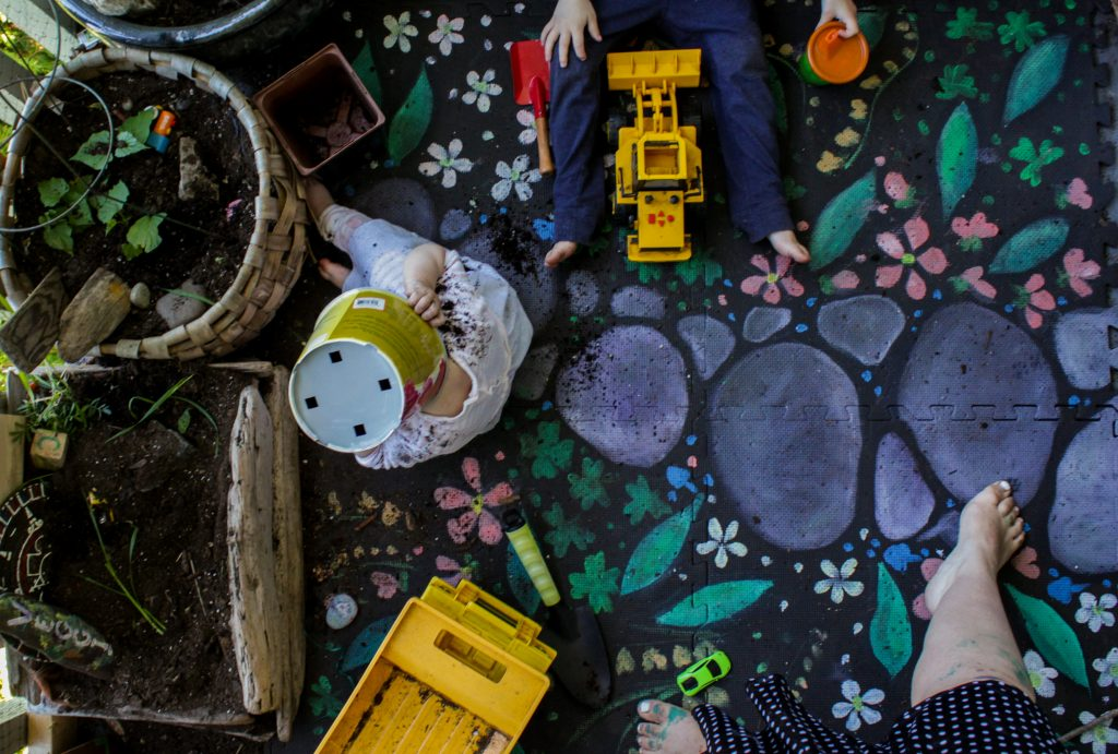 garden play mat painted with plants and rocks surrounded by toys and kids