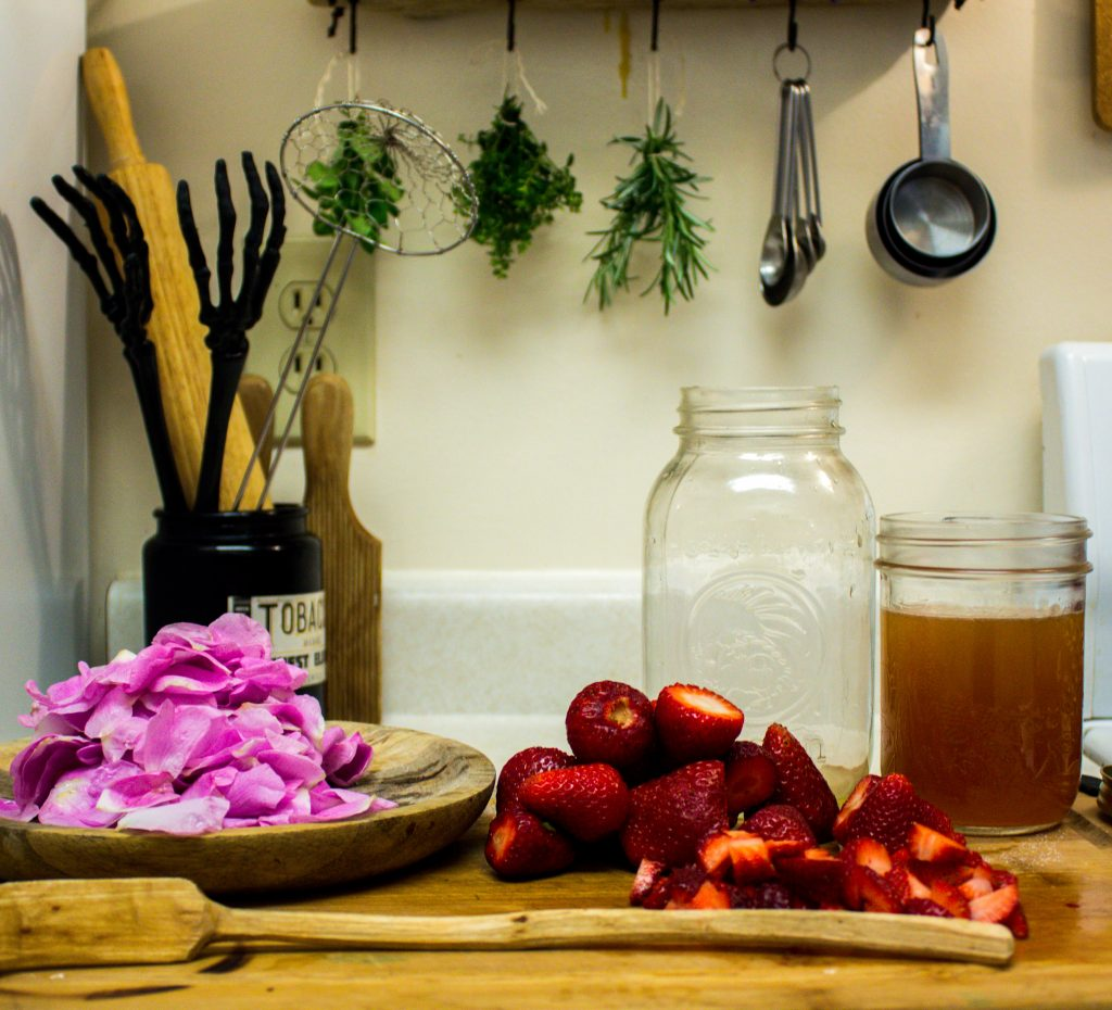 kitchen counter with utensils, herbs, mason jar, rose petals and strawberries