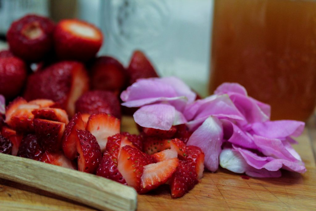 wild rose petals and strawberries on cutting board