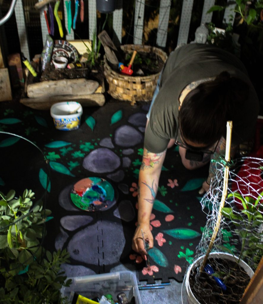 Woman painting a foam mat with acrylic paints in the night