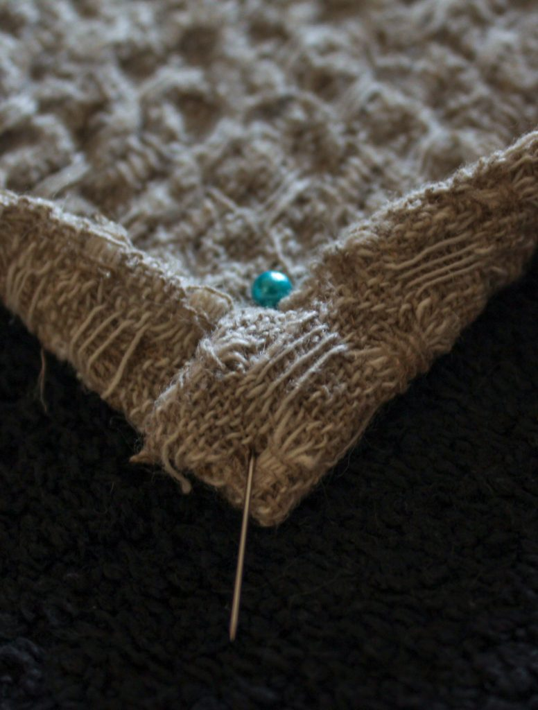 corner of linen tea towel pinned with blue pin