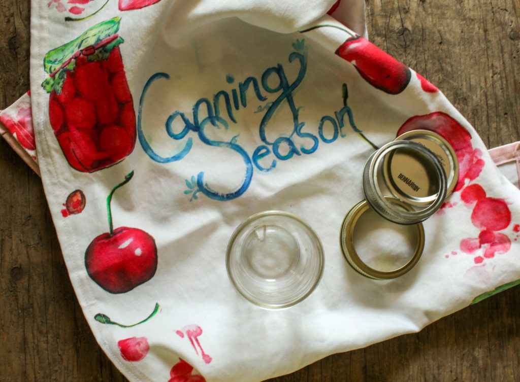tea towel with canning season written on it with pictures of cherries. wrapped around jar lids