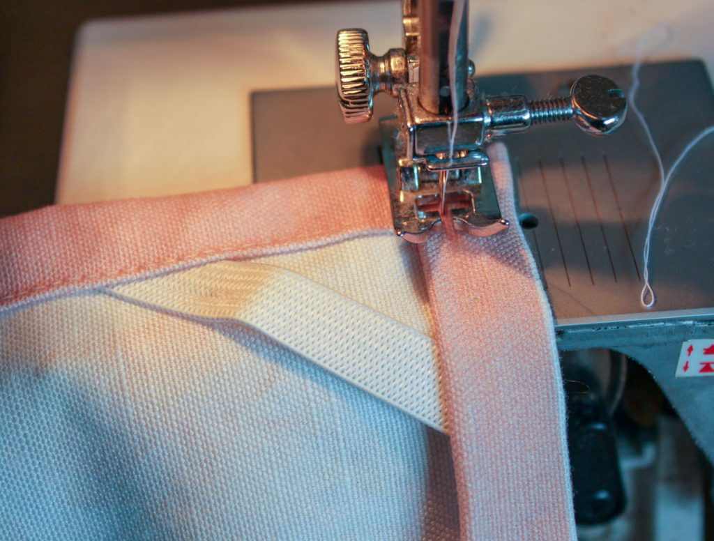 sewing machine close up sewing the cross band into tea towel seams