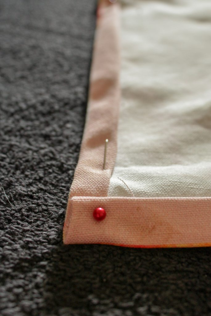 pinned corner of tea towel pinned with red pin