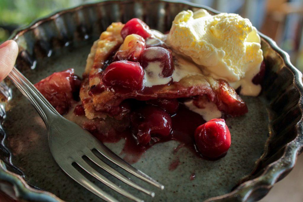 slice of sweet cherry pie with icecream on pttery