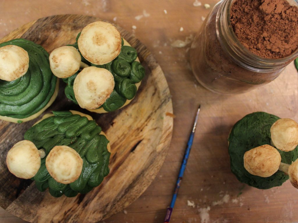 wooden plate with sweet rolls painting mushroom tops with cocoa powder