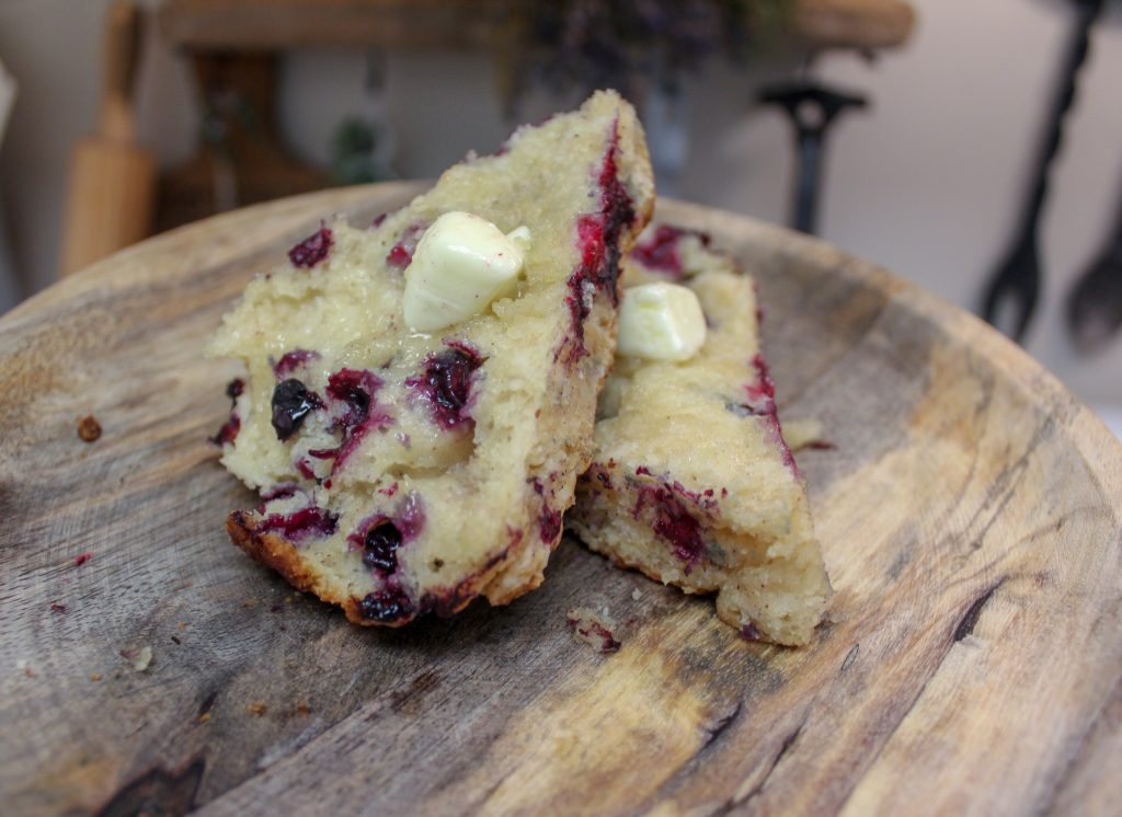 huckleberry scone cut in half with butter on wooden plate